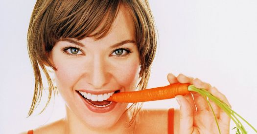 Young-woman-biting-carrot-smiling
